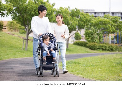 Japanese family pulled a stroller to walk in the park