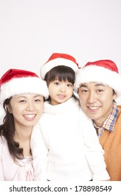 Japanese family smiling and wearing Santa hats