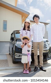 Japanese family standing in front of car