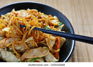 Japanese famous foods.Yakisoba. Stir-fried noodles with chicken and vegetables.Closeup of chopsticks with copy space for design work.Enjoy eating.Happy meal.Simple cooking with delicious menu at home
