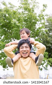 Japanese father and son playing with a shoulder car