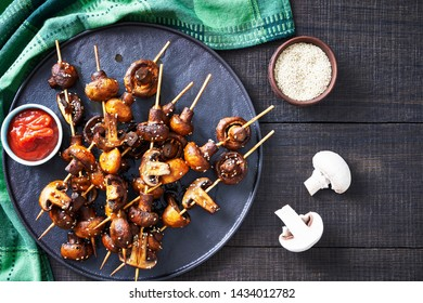 Japanese finger food: grilled champignon mushroom on skewers marinated in garlic and balsamic vinegar, sprinkled with sesame seeds, with ketchup on a black tray, close-up
