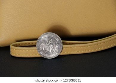 Japanese five hundred Yen coins on obverse (JPY) with sand color wallet on black floor, the concept of finance.