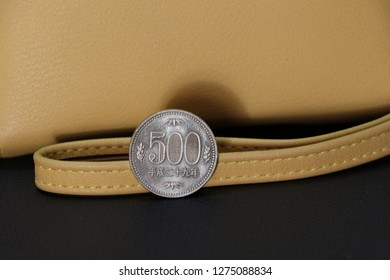 Japanese five hundred Yen coins on reverse (JPY) with sand color wallet on black floor, the concept of finance.
