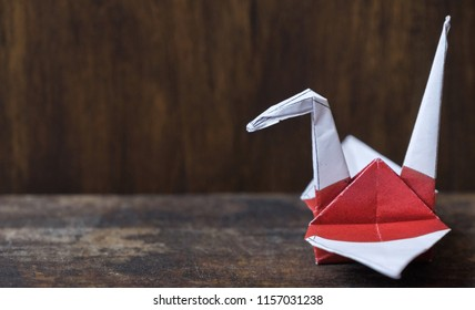Japanese flag origami paper crane on wooden table top