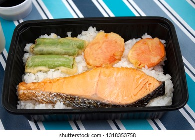 Japanese food bento box rice and fried salmon and vegetables with other cuisine on table in garden at outdoor of Japan village in Ayutthaya, Thailand