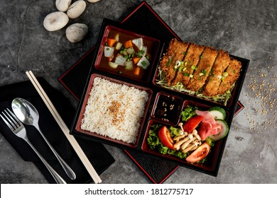 Japanese food bento set with tonkatsu and tempura on dark stone background