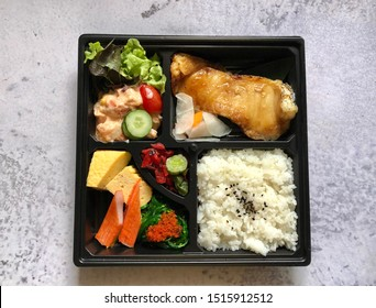 Japanese food box, fried fish, sweet eggs, seaweed with shrimp, salad, vegetable, sliced of cucumber, tomatoes and rice on plastic black tray on marble pattern table