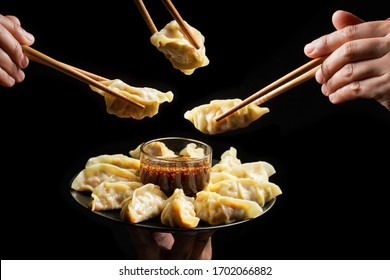 Japanese food called Gyoza dumplings with soy sauce on black background