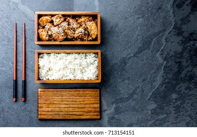 Japanese food. Chicken teriyaki with rice in wooden bento lunch box. slate background, top view