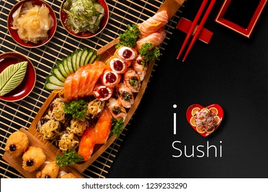 Japanese food combo in black background.itten I love Sushi in english. Top view