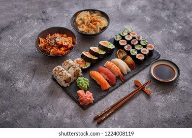 Japanese food composition. Various kinds of sushi placed on black stone board. Spicy kimchi salad, wontong soup, chopsticks and soy souce bowl.