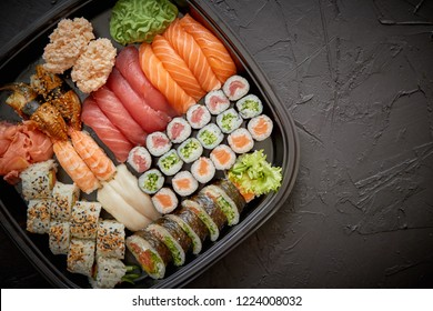 Japanese food concept. Catering, various kinds of sushi on plate or platter set. Chopsticks, ginger, soy sauce, wasabi. Placed on stone black background in plastic delivery box.