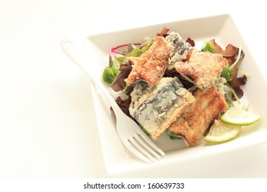 Japanese food, deep fried Pacific saury on baby leaf salad for autumn gourmet image