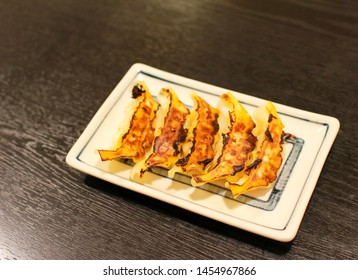Japanese food, Gyoza (dumplings filled with vegetables and meat) on a white square plate on a black table