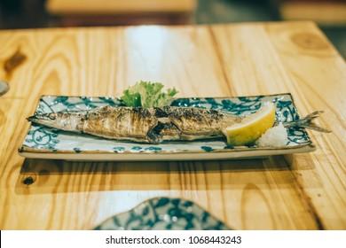 Japanese food in izakaya restaurant at night. Grilled sanma fish.