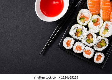 Japanese food: maki and nigiri sushi set on black background. Flat lay top-down composition. Copyspace