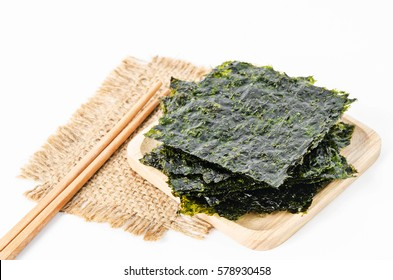 Japanese food nori dry seaweed sheets with salt and chopsticks on white background.