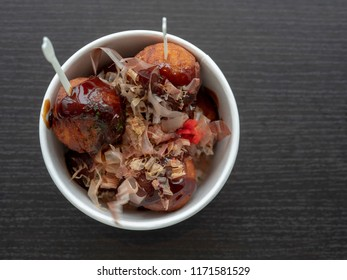 Japanese food octopus dumpling in paper cup on black table, Top view