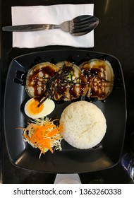 Japanese food, rice, kurobuta pork and half boiled egg on black dish