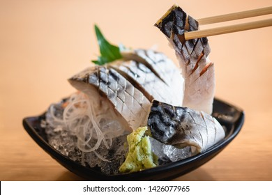 Japanese Food : Saba Sashimi, raw fresh pieces of fermented mackerel on a black dish of ice with wasabi on wooden table