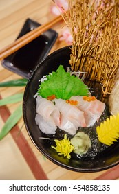 Japanese food Sashimi raw fish on ice hamachi or otoro in bow on wood table.