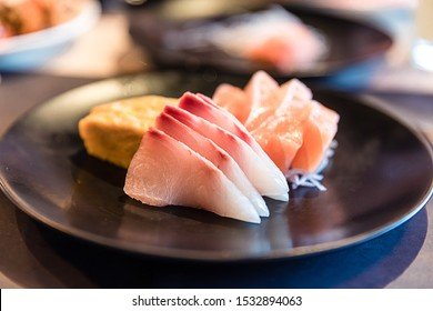 Japanese food sashimi (raw sliced fresh fish),Tai sashimi or Suzuki sashimi (sea bream fish, red snapper or sea bass fish), salmon and tamagoyaki (sweet egg or Japanese omelette) on black plate