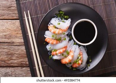Japanese food: Shirataki with prawns, spring onions and soy sauce on a plate close-up. Horizontal view from above