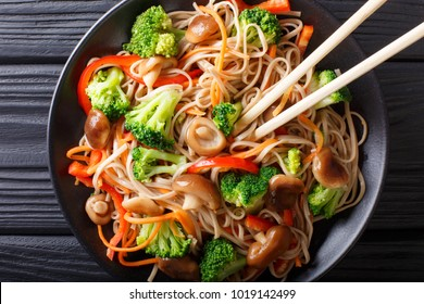 Japanese food: Soba noodles with mushrooms, broccoli, carrots, peppers close-up on a plate on the table. Horizontal top view from above