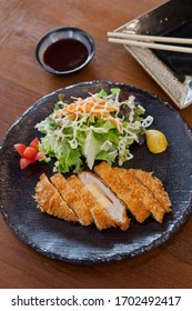 Japanese food style. Fired  Chicken  with cheese inside and vegetables ,sauce in.Black plate on wooden.table.