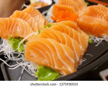 Japanese food style, Top view of salmon slice on radish and lettuce on black plate, Salmon sashimi is Japanese traditional, Selective focus