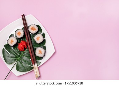 Japanese Food Sushi with Salmon and Ginger on White Plate With Tropical Leaves Pink Background Top View Copy Space