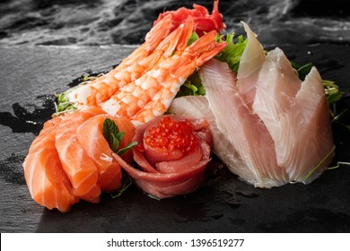 japanese foods sashimi. Mixed sliced fish sashimi in dark background. Sashimi Salmon and Tuna set with Tuna, shrimps flying fish roe caviar and Foie Gras closeup. Japan restaurant menu