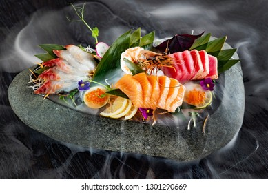 japanese foods sashimi (raw sliced fish, shellfish or crustaceans) with smoke on the black background