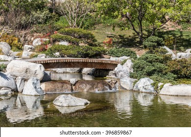Japanese garden bridge over a pond. Trees and shrubbery. Reflections of rocks in water.