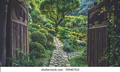 A Japanese garden with large, wooden doors