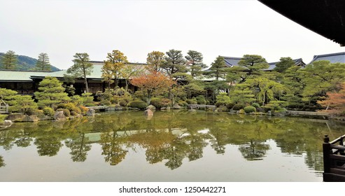 A Japanese garden with a pavilion, and trees facing the lake, thus casting reflections in the water.