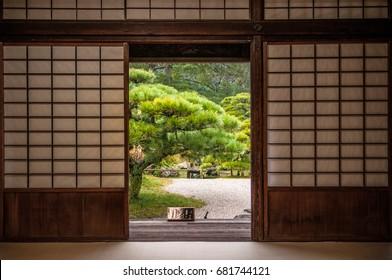 Japanese garden and pine tree seen through sliding door.
