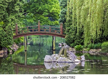 japanese garden - a pond, artificial island, and red bridge - taiko bashi, characteristic element of japanese gardens shadowed by trees