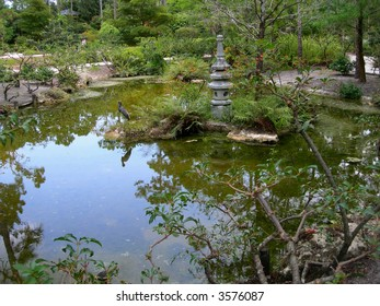 Japanese garden with pond and traditional sculpture