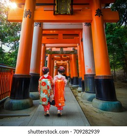 Japanese Geisha in Full Traditional Kimono Dress Walk Through Torii Gates at Fushimi Inari Taisha Shrine in Kyoto, Japan
