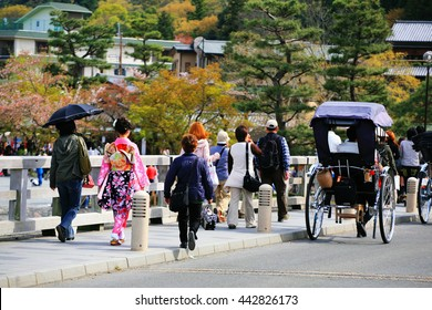 Japanese girl with beautiful kimino at Arashiyama bridge to enjoy cherry blossom, Hanami, in Kyoto, Japan