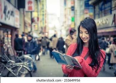 japanese girl consulting the tokyo city map. concept about tourism