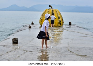 a japanese girl dressed in school uniform immerses her legs in a lake during a class trip