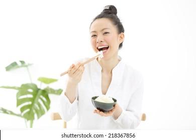 Japanese girl eating rice with sticks, isolated on white background
