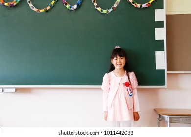 Japanese girl in elementary school standing at board after entrance ceremony