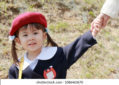 Japanese girl in kindergarten uniform clasping her mother's hand (3 years old)