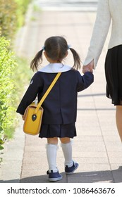 Japanese girl in kindergarten uniform clasping her mother's hand (3 years old) (retreating figure)