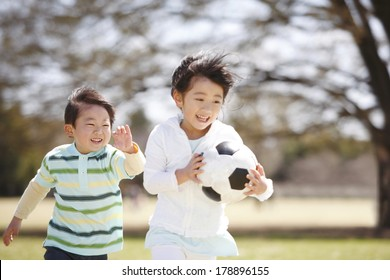 Japanese girl running with a soccer ball