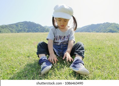 Japanese girl sitting on the lawn (3 years old)